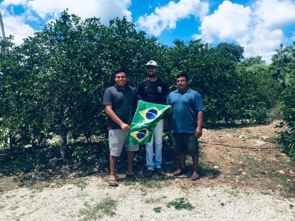 Flávio segura bandeira do Brasil ao lado de dois homens em plantação