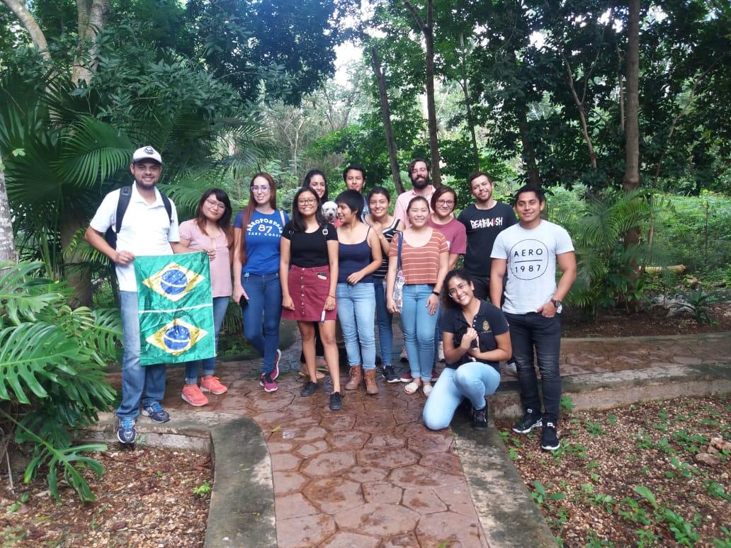 Flavio segura a bandeira do Brasil ao lado de voluntários do projeto