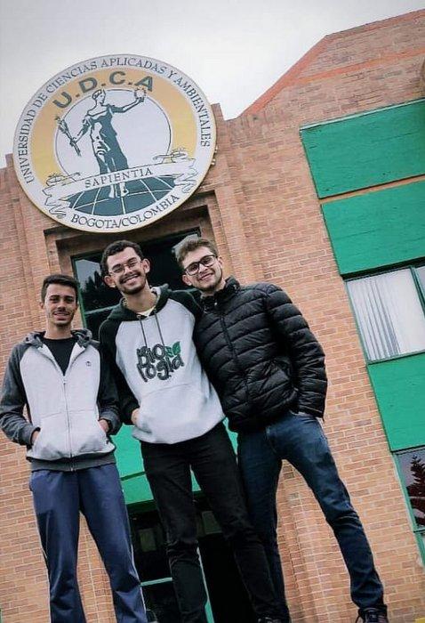 João posa ao lado de dois jovens em frente à entrada da universidade