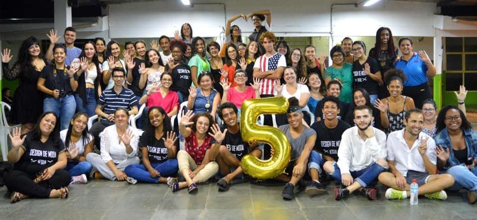 Estudantes estão reunidos envolta de um balão do número 5 dourado