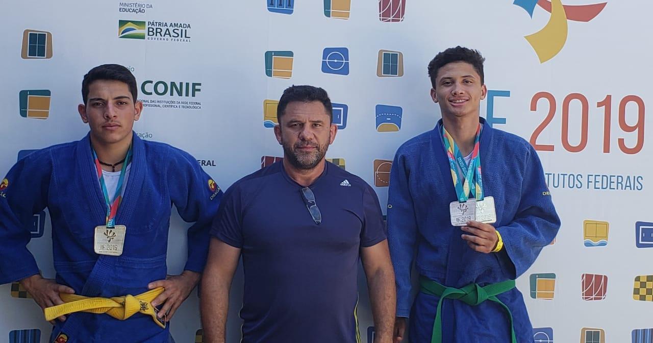 Dois judocas e o coordenador de esportes do IFSULDEMINAS mostram medalhas