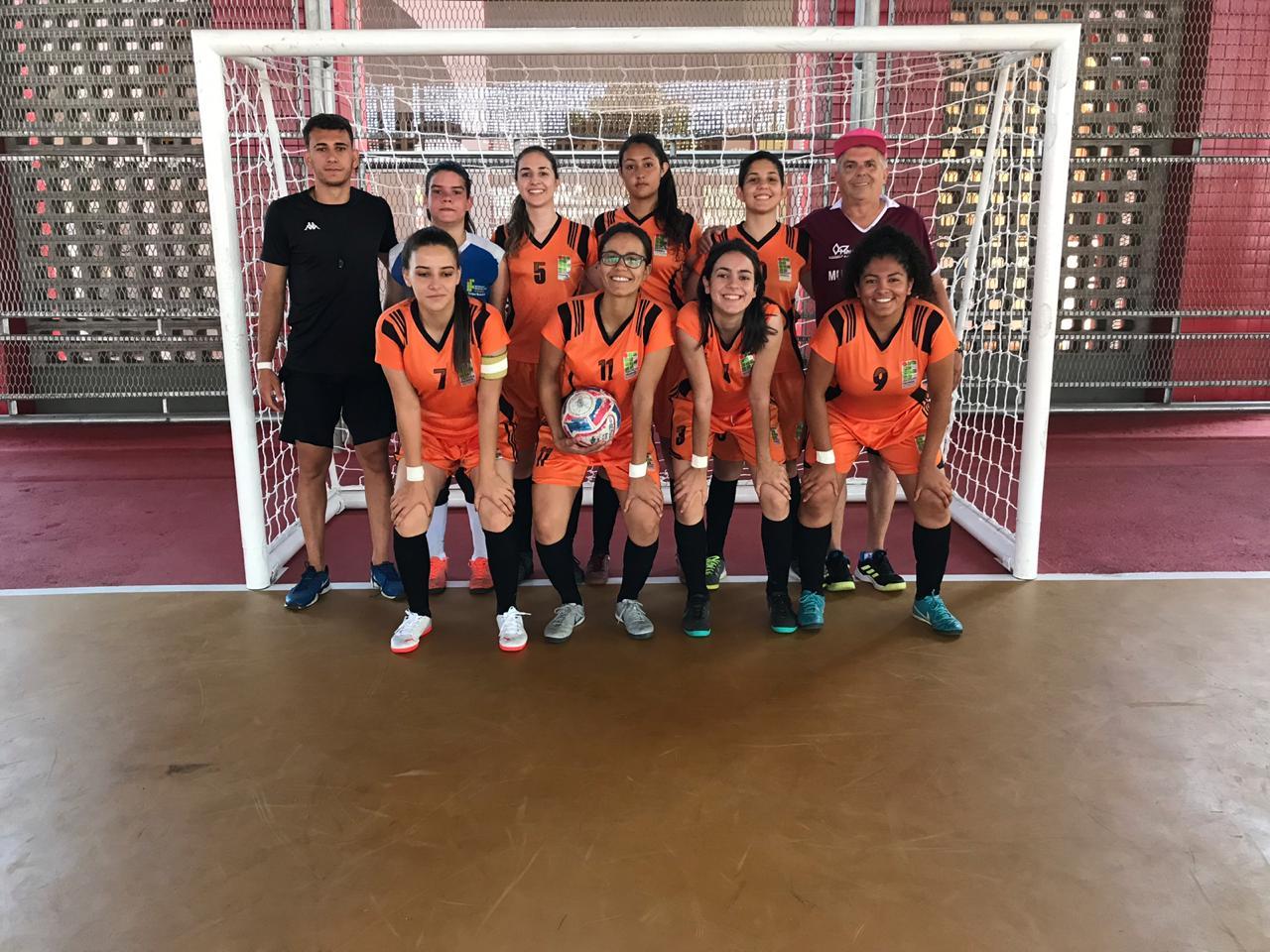 Jogadoras de futsal do IFSULDEMINAS e equipe técnica posam para foto em frete ao gol