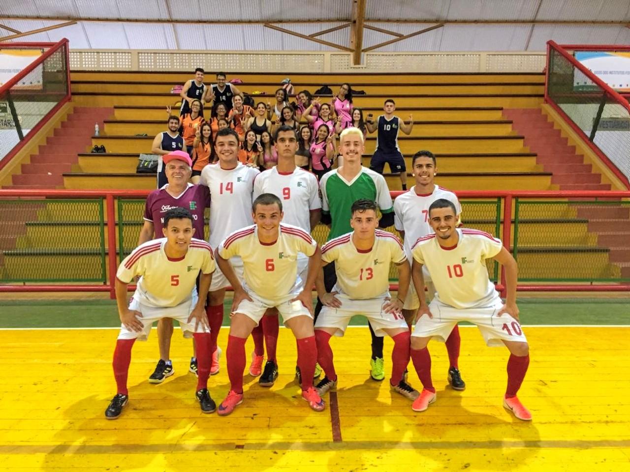 Jogadores e técnico da equipe de futsal do IFSULDEMINAS posam para foto em frente à arquibancada