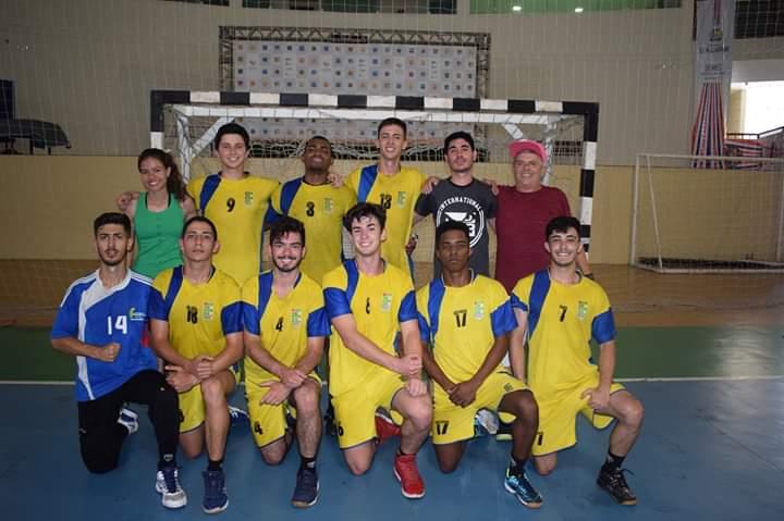 Na quadra jogadores e equipe técnica do time de handball do IFSULDEMINAS posam em frente ao gol