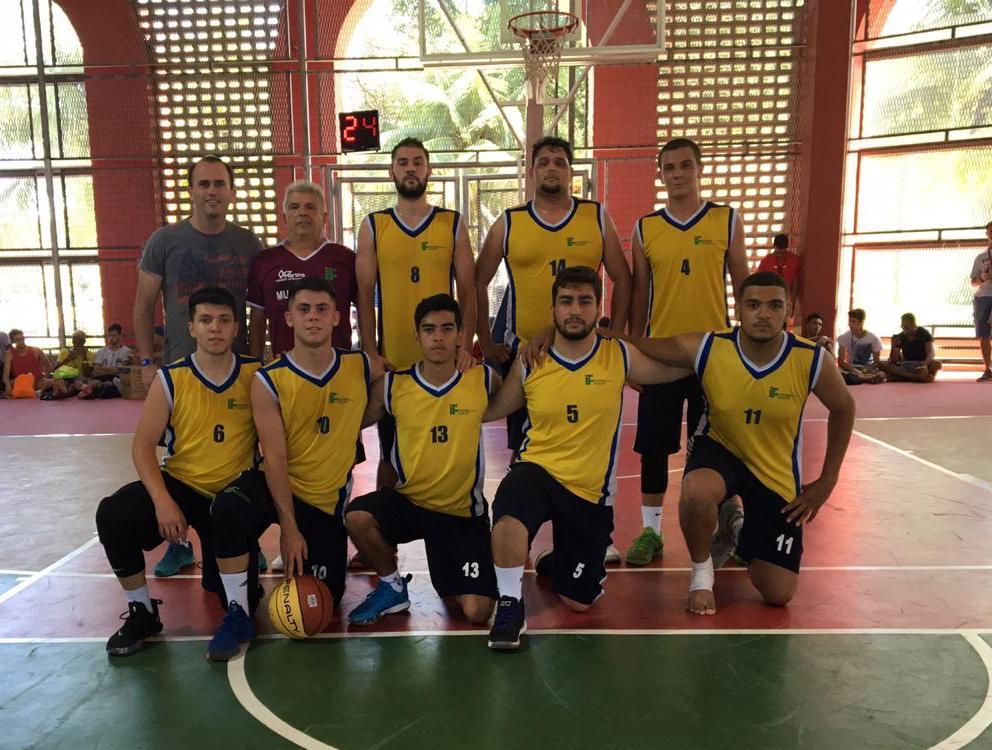 Todos uniformizados jogadores e equipe técnica do time de basquete do IFSULDEMINAS posam para foto na quadra